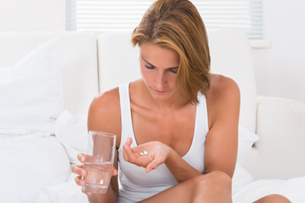 Young Woman In Tanktop Holding Medicine And Glass Of Water