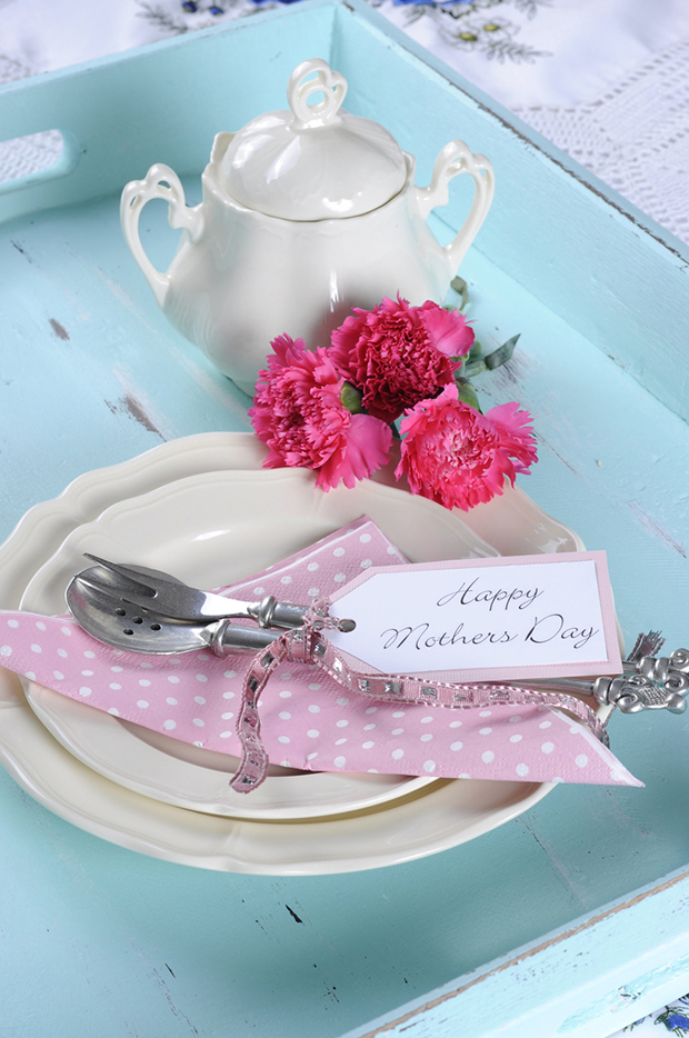 Happy Mothers Day aqua blue breakfast morning tea vintage retro shabby chic tray setting with antique fine china plates, pink carnations and sugar bowl.